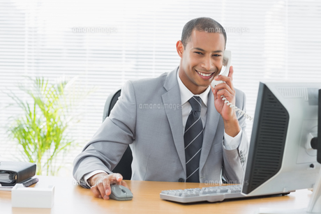 Businessman using computer and phone at office deskの素材 [FYI00000001]