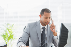 Businessman using computer and phone at officeの写真素材 [FYI00000002]