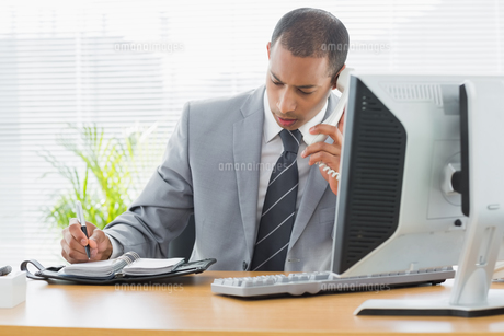 Businessman using computer and phone at office deskの素材 [FYI00000003]