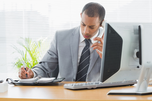 Businessman using computer and phone at office deskの写真素材 [FYI00000003]