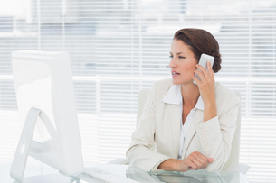 Businesswoman using computer and cellphone at deskの写真素材 [FYI00000005]