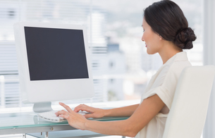 Young businesswoman using computer in officeの写真素材 [FYI00000007]