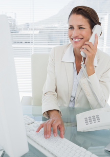 Smiling businesswoman using computer and phoneの写真素材 [FYI00000008]