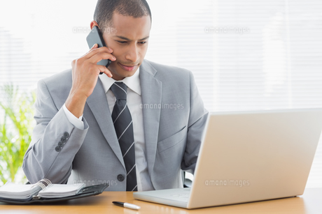 Businessman using laptop and cellphone at officeの素材 [FYI00000010]