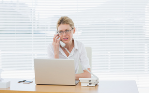 Businesswoman using laptop and phone at deskの写真素材 [FYI00000014]