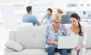 Women using laptop with colleagues in background at creative officeの写真素材 [FYI00000021]