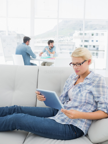 Woman using digital tablet with colleagues in background at creative officeの写真素材 [FYI00000022]