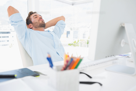 Casual man resting with hands behind head in officeの素材 [FYI00000028]