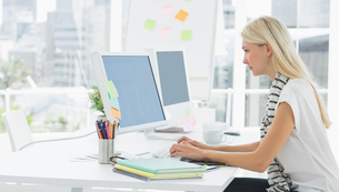 Casual young woman using computer in officeの写真素材 [FYI00000046]