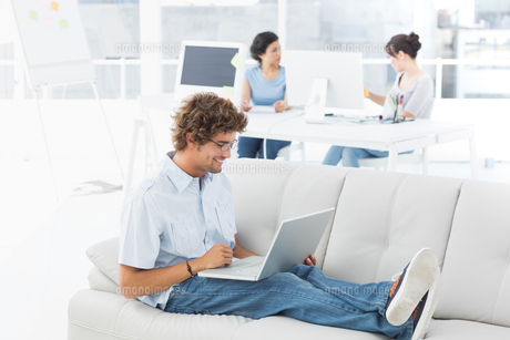 Man using laptop with colleagues at creative officeの写真素材 [FYI00000048]