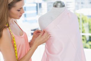 Beautiful female fashion designer working on pink fabricの写真素材 [FYI00000055]