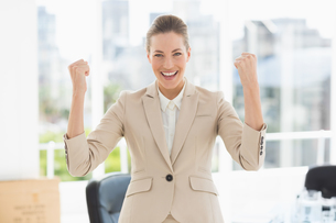 Cheerful businesswoman clenching fists in officeの写真素材 [FYI00000063]
