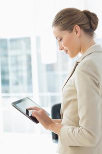 Beautiful businesswoman using digital tablet in officeの写真素材 [FYI00000070]