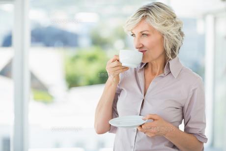 Smiling beautiful businesswoman drinking teaの素材 [FYI00000078]