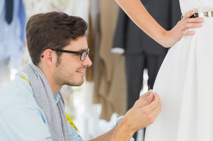 Male fashion designer adjusting dress on modelの写真素材 [FYI00000099]