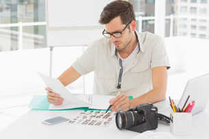 Concentrate male artist sitting at desk with photosの写真素材 [FYI00000112]