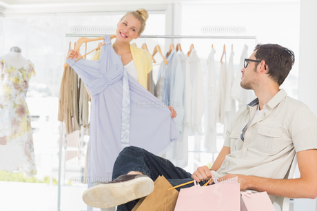 Man with shopping bags while woman selecting a dressの写真素材 [FYI00000118]