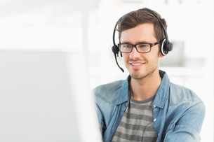 Smiling casual young man with headset using computerの写真素材 [FYI00000119]
