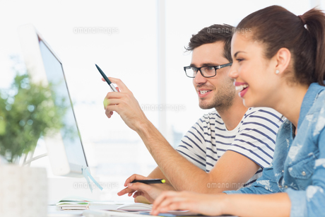 Happy young couple working on computer in an officeの写真素材 [FYI00000125]