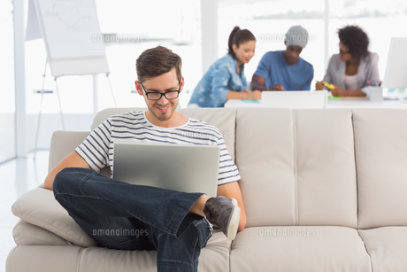 Man using laptop with colleagues in background at creative officeの写真素材 [FYI00000135]