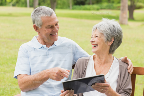 Cheerful senior couple using digital tablet on bench at parkの写真素材 [FYI00000140]
