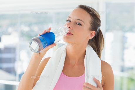 Woman with towel drinking water in gymの写真素材 [FYI00000160]