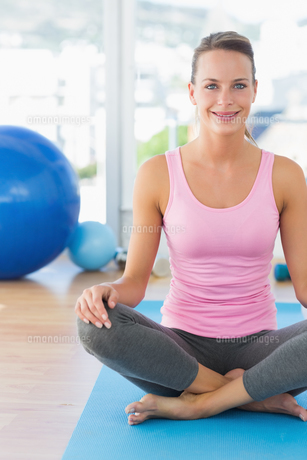 Smiling young woman sitting at fitness studioの素材 [FYI00000165]