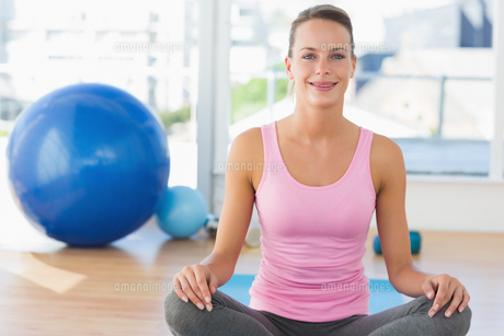 Smiling young woman sitting at fitness studioの写真素材 [FYI00000166]