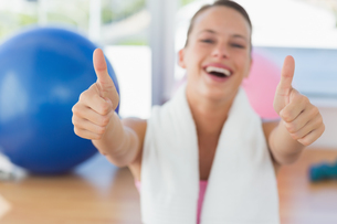 Woman with towel gesturing thumbs up in gymの写真素材 [FYI00000168]