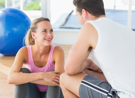 Smiling fit couple chatting in exercise roomの写真素材 [FYI00000169]