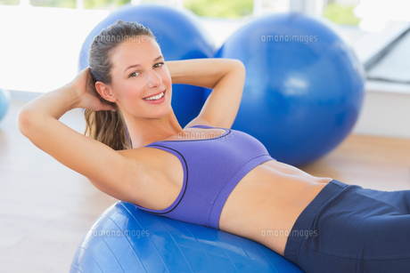 Side view portrait of a smiling fit woman lying on exercise ballの素材 [FYI00000175]
