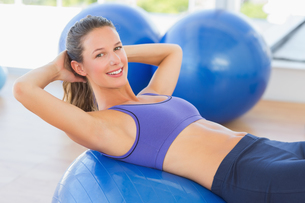 Side view portrait of a smiling fit woman lying on exercise ballの写真素材 [FYI00000175]