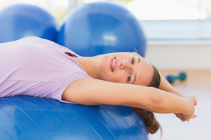 Smiling fit woman lying on exercise ball at gymの写真素材 [FYI00000176]