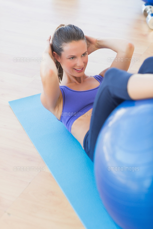 Fit young woman exercising on fitness ballの写真素材 [FYI00000177]
