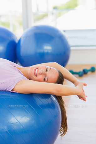 Smiling fit woman lying on exercise ball at gymの素材 [FYI00000178]