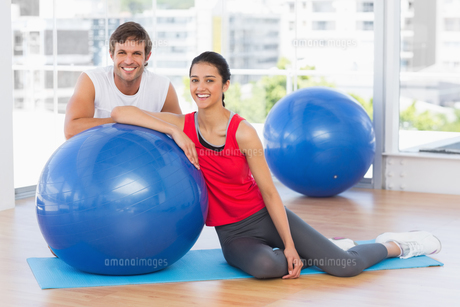 Smiling fit young couple with exercise ball at gymの写真素材 [FYI00000179]