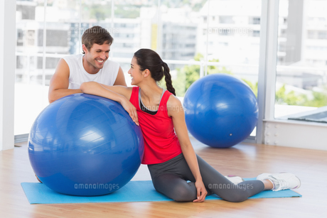 Smiling fit young couple with exercise ball at gymの素材 [FYI00000180]