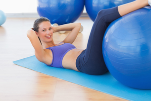 Fit young woman exercising on fitness ballの写真素材 [FYI00000181]