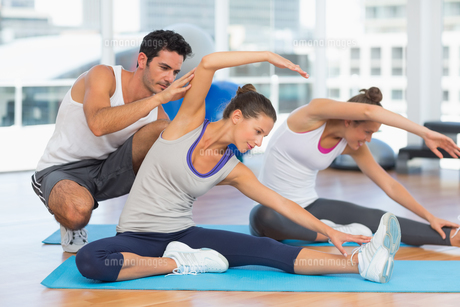 Women doing stretching exercises as trainer helps oneの写真素材 [FYI00000185]