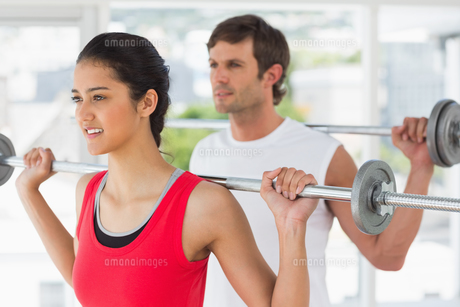 Fit young couple lifting barbells in gymの写真素材 [FYI00000188]