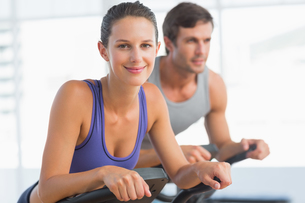 Smiling young couple working out at spinning classの写真素材 [FYI00000191]
