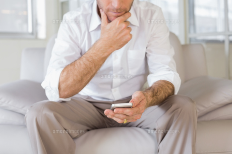 Mid section of man text messaging at homeの写真素材 [FYI00000193]