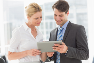 Business team looking at tablet pc togetherの写真素材 [FYI00000194]