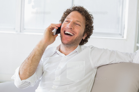 Cheerful man using mobile phone at homeの写真素材 [FYI00000196]