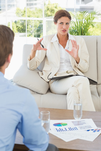 Businesswoman talking with colleague sitting on sofaの写真素材 [FYI00000202]
