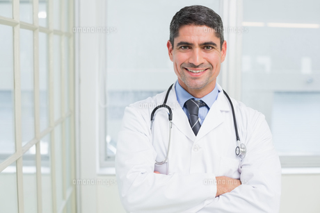Smiling male doctor with arms crossed in hospitalの写真素材 [FYI00000203]
