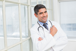 Smiling male doctor with arms crossed in hospitalの写真素材 [FYI00000205]