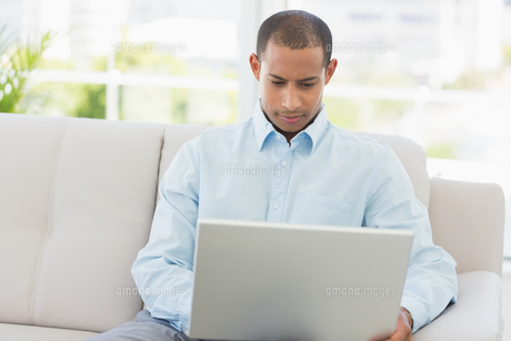 Young businessman working on laptop on the couchの写真素材 [FYI00000206]