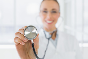 Blurred smiling female doctor with stethoscopeの写真素材 [FYI00000207]