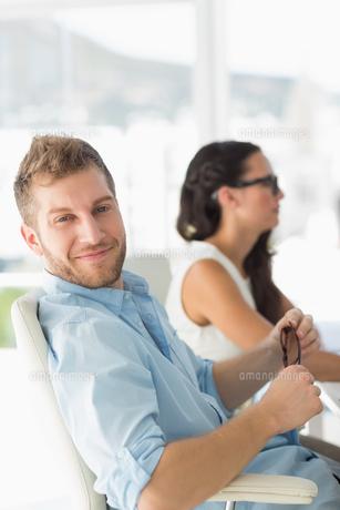 Happy designer smiling at camera at deskの写真素材 [FYI00000211]